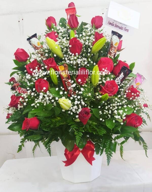 Ramo en rosas rojas en forma de triángulo mas lirios decorado con. Follaje verde y chocolates