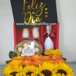 Bella caja decorada con champagne con copas, corazón de Ferrero rosas y girasoles hermosa